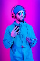 Funky young bearded hipster man in glasses and headphones dances and listens pleasurable music in his smartphone. love live. Leisure hobby mood concept. Relax.
