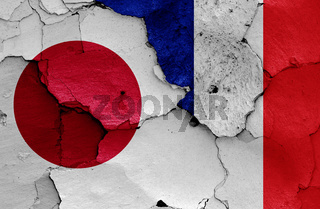 flags of Japan and France painted on cracked wall