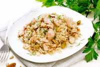 Salad of salmon and rice in plate on white board