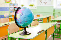 Earth globe on the yellow desk at classroom