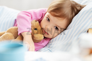 little girl lying in bed at home