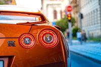 PRAGUE, CZECH REPUBLIC, JULY 2020 - Rear lights of Orange Nissan Skyline GTR on a street waiting for green light