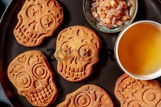 Halloween ginger cookies in the shape of skulls, close-up, homemade Dia de los muertos biscuits, overhead shot
