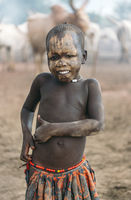 MUNDARI TRIBE, SOUTH SUDAN - MARCH 11, 2020: Kid in traditional colorful clothes and accessories smiling at camera while standing against blurred cattle in village in South Sudan in daytime