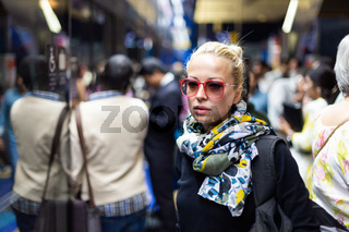 Young woman wearing colorful scarf waiting on the platform of a urban metro station for train to arrive. Public transport