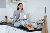 Image of cute brunette woman sitting at kitchen and using laptop