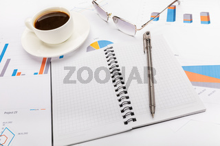 Notepad, a pen, coffee and glasses in business or school concept