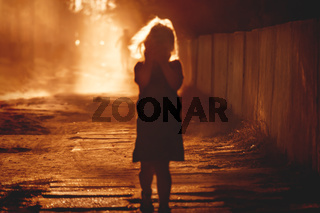 Defocused silhouette of a child covering her face with the hands and blurred person running into light at in the back