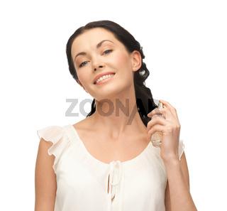 woman spraying pefrume on her neck