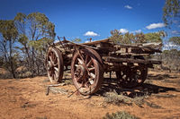 Australia – Outback savanna with an old vintage derelict horse-drawn carriage at the bush under blue sky