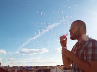 Man blowing soap bubbles from his balcony. Exit restriction quarantine due to coronavirus, home offi