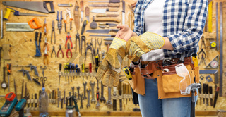 woman or builder with gloves and working tools