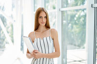 Confident business woman holding documents and looking at camera in modern office