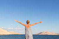 Happy carefree woman rising arms, wearing beautiful striped summer dress enjoying late afternoon on white pabbled beach on Pag island, Croatia