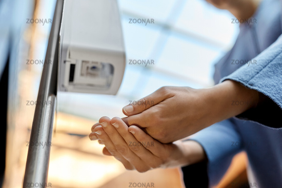 close up of woman at dispenser with hand sanitizer