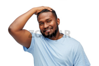 smiling young african american man touching hair