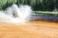Man driving motocross ATV quad through splashing river lake water with high speed. Foy, Foyross Lake, Sudbury, Canada.