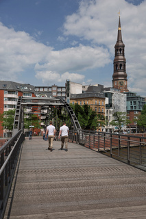 People crossing bridge and city life in Hamburg in Germany with St. Catherine's church in the background