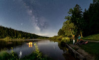 Friends are taking an outdoor bath in a lake under the nightly milkyway at a star clear night, beautiful summer scene.