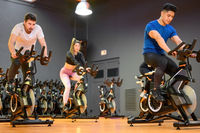 Group cycling on a modern fitness bicycle during group spinning class at the gym
