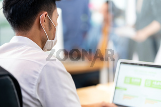 Asian employee face mask in social distance new normal office