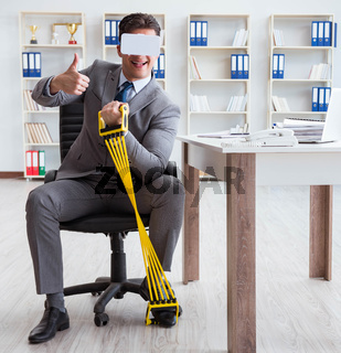 Businessman exercising with elastic expander wearing VR glasses