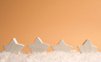 Four white wooden star shapes with snow on an orange paper background, space for text on top