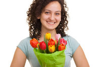Young natural woman with curly hair holding a bouquet of colorful tulips, isolated on white background. Mothers day, Valentines day, Easter Concept.