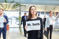 Geschäftsfrau mit Namensschild am Flughafen