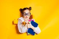 Smart schoolgirl looking through hole in yellow paper. Back to school.