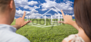 Couple Framing Hands Around House Figure in Grass Field