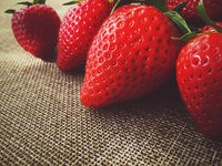 Organic strawberries on rustic linen background