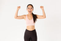 Sport, wellbeing and active lifestyle concept. Empowered and strong asian female athlete, fitness girl encourage herself for good workout, fist pump and shouting upbeat, white background