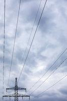 Strommast mit Leitungen bei dramatischem Himmel