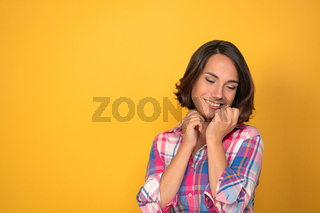 Charming woman expressing tenderness and saying good bye in plaid shirt on a yellow background with copy space. Facial expressions, emotions, feelings