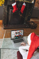 Rear view of woman in santa hat having a videocall with senior couple in santa hats opening gift box