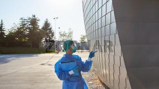 Containment Scout vor Klinik macht Handzeichen am Eingang für Einlass Kontrolle