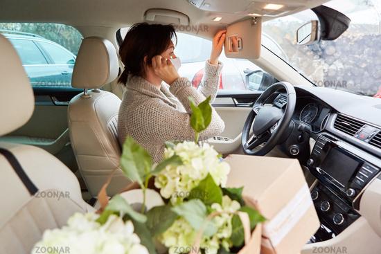 Auto Fahrerin mit Mundschutz macht Anruf als Bringdienst