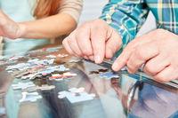 Hände von Senioren beim Puzzle spielen