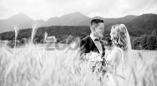 Groom hugs bride tenderly in wheat field somewhere in Slovenian countryside.