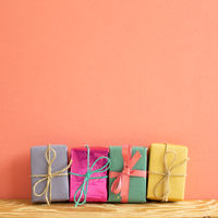 Colorful gift boxes on wooden table with coral pink background