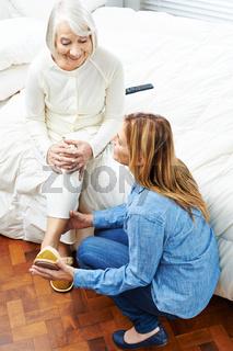 Frau hilft Seniorin beim Anziehen