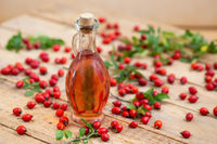 A bottle of rose hip oil with red berries in background.