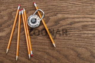 Pencils and lock on wood surface