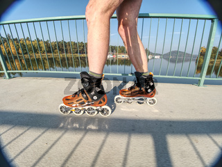Roller skater ride in park. Boy legs in in-line hard shell boots blades.