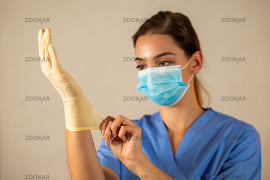 Young nurse with blue surgical mask wearing protective rubber gloves.