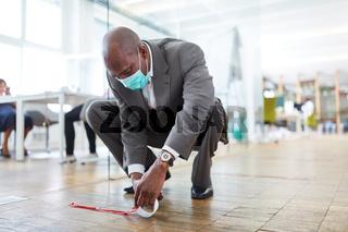 Geschäftsmann markiert Büro Boden mit Klebeband