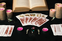 Candles and old tarot cards on black silk