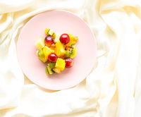 Fresh fruit vegan salad on a pink plate, healthy nutrition and detox