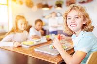 Kinder essen in Cafeteria einer Schule Obst
